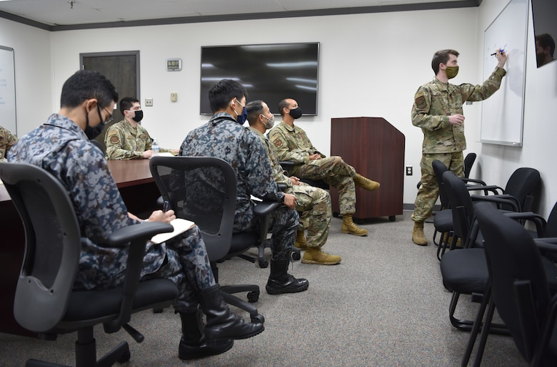 The 552d Air Control Networks Squadron's Mission Defense Team is comprised of cyber operators from a variety of different backgrounds, all contributing their unique skillsets to the team. When tasked for a cyber defense mission, a MDT crew plans and briefs the mission before operating on an AWACS or Control and Reporting Centers cyber terrain, just like an aircrew. The 552d ACNS has been the only MDT in the Air Force to perform missions inside the skin of an aircraft, defending against adversaries in cyberspace. Senior Airman Gabriel Coleman, 552nd ACNS, describes the mission to Lt. Col. Akio Ohigashi and Capt. Shumpei Kawano from the Japan Air Self-Defense Force and Capt. Ali Syed, and Master Sgt. Christopher Bailey, U.S. Pacific Air Forces Cyber Defense and Mission Assurance. (U.S. Air Force photo by Kimberly Woodruff)