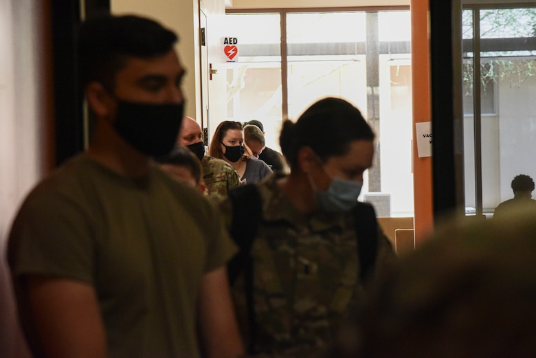A photo of servicemembers waiting in line to receive a vaccine.