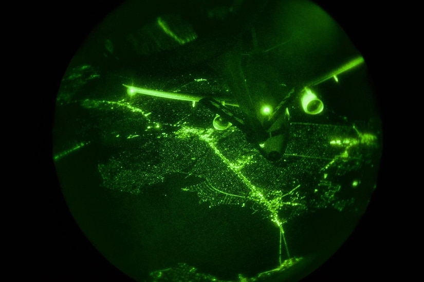 Seen on a night vision scope, a military aircraft approaches the refueling boom of another aircraft.