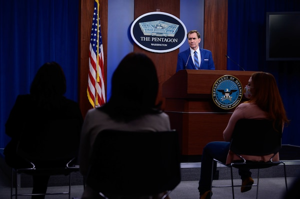 """A man stands behind a lectern. Behind him is a sign that reads """"The Pentagon -- Washington."""" In front of him are seated individuals."""