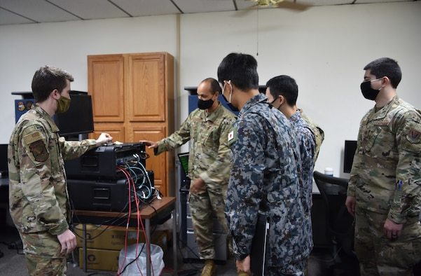 Senior Airman Gabriel Coleman, 552 Air Control Networks Squadron, and Master Sgt. Christopher Bailey, Pacific Air Command A3/6, explain the capabilities of a deployable cyber defense weapon system, Cyberspace Vulnerability Assessment/Hunter, to Lt. Col. Akio Ohigashi and Capt. Shumpei Kawano from the Japanese Air Self-Defense Force. The system is used by the 552 ACNS Mission Defense Team to defend the 552nd Air Control Wing's Control & Reporting Centers and E-3 fleet and ground systems from cyber threats. (Air Force photo by Kimberly Woodruff)