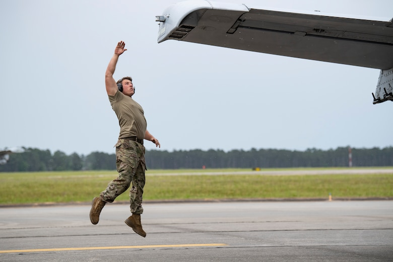 A photo of an Airman jumping to touch the wing tip of an aircraft