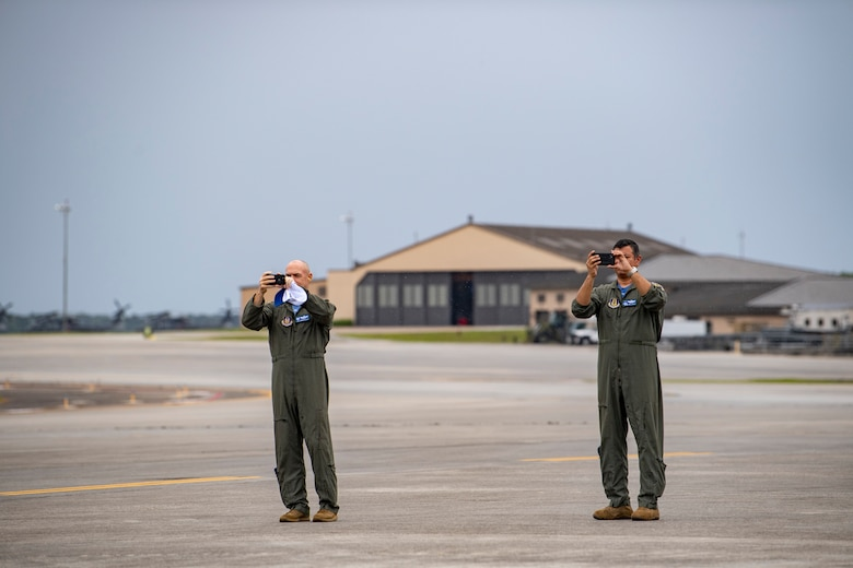 A photo of Airmen taking video of aircraft