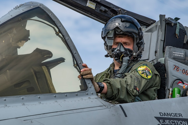 A photo of a pilot posing in a cockpit