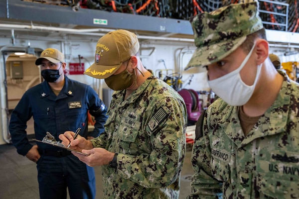 Capt. Todd Whalen, chief of staff, Naval Surface Force Atlantic fills out forms prior to receiving the COVID-19 vaccine aboard the San Antonio-class amphibious transport dock ship USS Arlington (LPD 24), April 23, 2021.