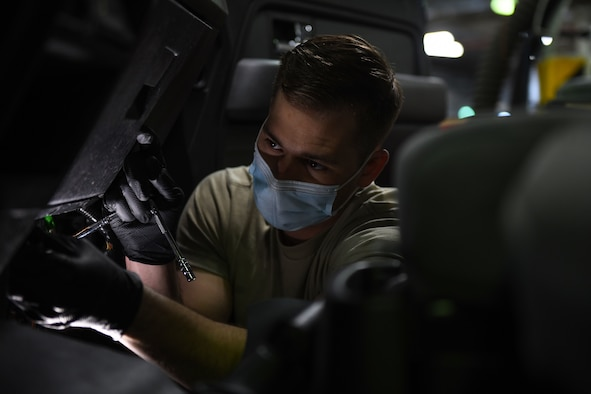 Airman 1st Class Korey Sarantopoulos, 31st Logistics Readiness Squadron vehicle maintenance technician, uses a flashlight to inspect a Ford F-150 at Aviano Air Base, Italy, April 20, 2021. Sarantopoulos repaired the heat, ventilation, and air conditioning (HVAC) system of a Ford F-150 truck. The HVAC system took approximately eight hours to repair. (U.S. Air Force photo by Senior Airman Ericka A. Woolever.)