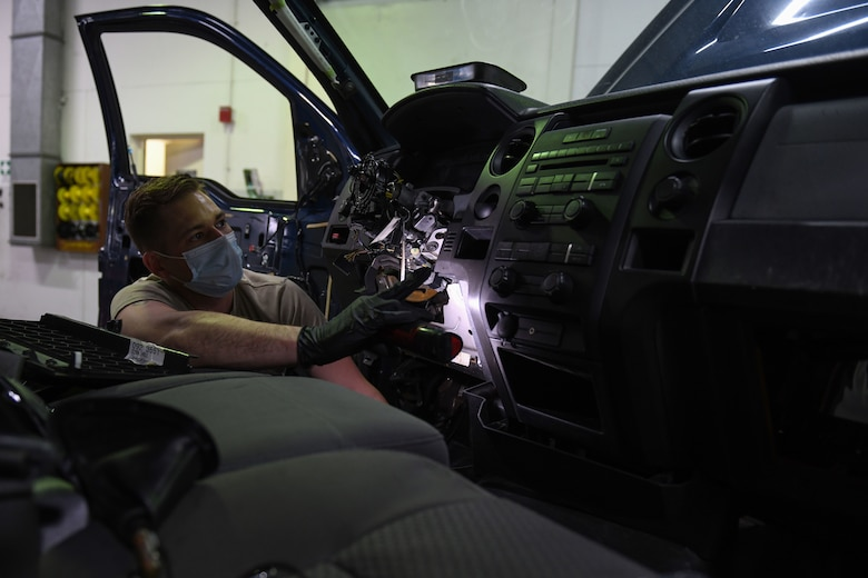 Airman 1st Class Korey Sarantopoulos, 31st Logistics Readiness Squadron vehicle maintenance technician, inspects a Ford F-150 truck at Aviano Air Base, Italy, April 20, 2021. Sarantopoulos repaired the heat, ventilation, and air conditioning (HVAC) system of a government vehicle. Sarantopoulos extracted multiple parts of the vehicle, such as the steering wheel and radio to repair the HVAC system. (U.S. Air Force photo by Senior Airman Ericka A. Woolever)