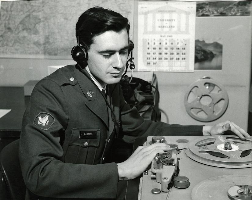 A uniformed man in headphones touches DJ equipment in a radio studio.