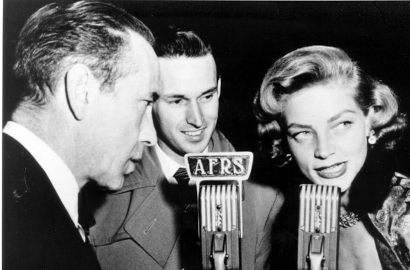 """A woman and two men stand in front of a 40s-era microphone that says """"AFRS."""""""