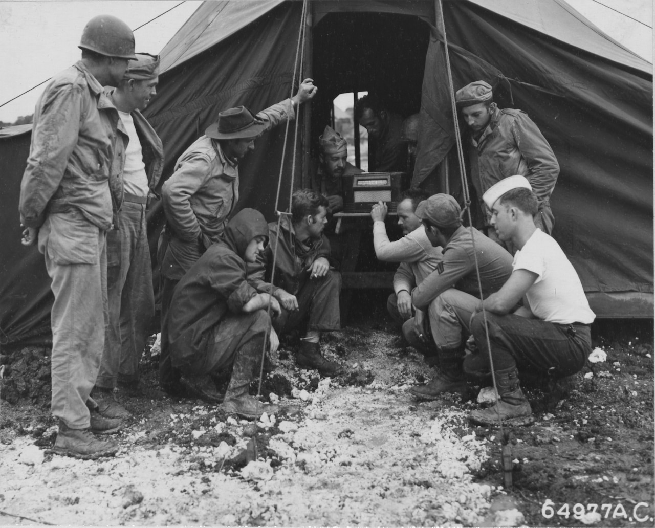 Several men crowd around a 1940s-era radio sitting just inside a tent.