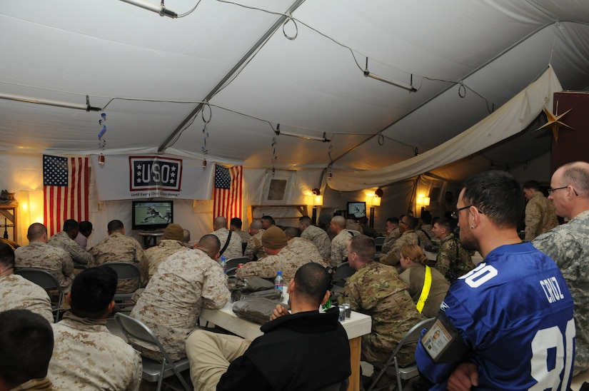 Several seated people surround a small TV in a tent.