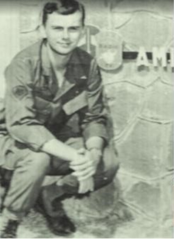 A man in uniform squats down to pose near a sign that's cut off.