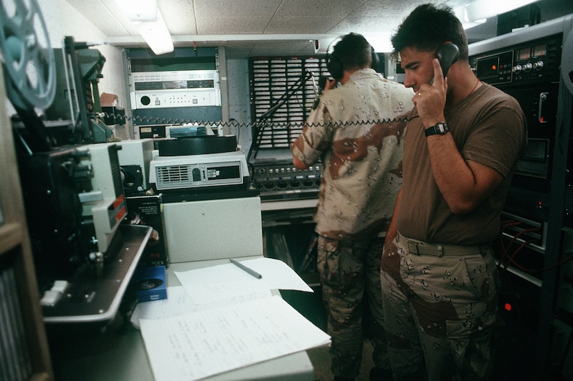 A man in fatigues is on the phone while another man dons headphones in a small studio.