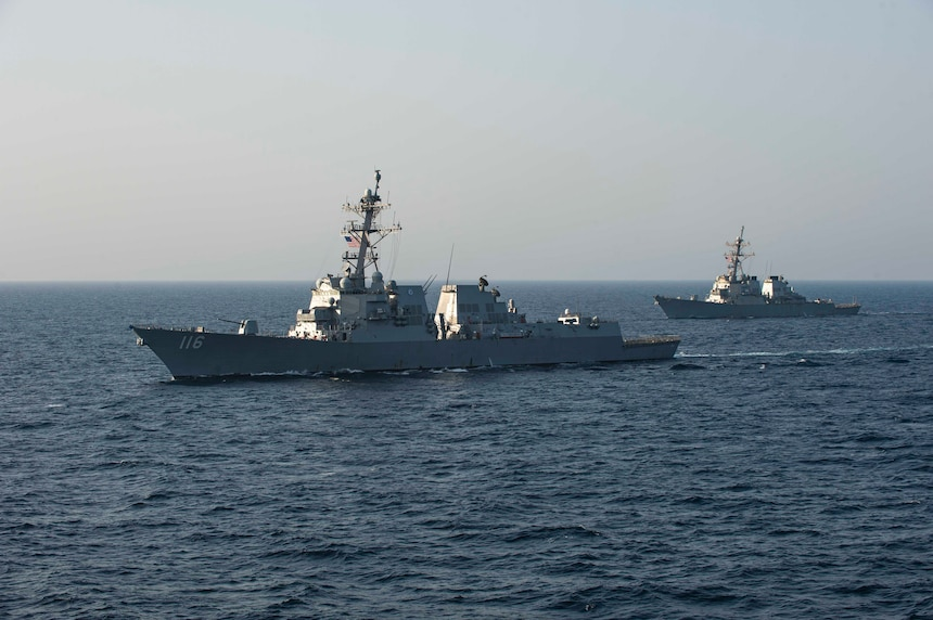 USS Thomas Hudner (DDG 116) and  USS Laboon (DDG 58) sail in formation alongside the aircraft carrier USS Dwight D. Eisenhower (CVN 69) in the Arabian Sea.