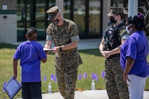 U.S. Marine Corps Col. Curtis V. Ebitz, center, the commanding officer of Marine Corps Air Station New River, hands out an award during a ceremony at Delalio Elementary School on MCAS New River, North Carolina, April 8, 2021. April is the month of the military child, highlighting the important role military children play in the armed forces community. (U.S. Marine Corps photo by Lance Cpl. Isaiah Gomez)