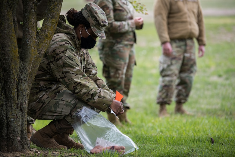Senior Airman Tierra Brown, 22nd Force Support Squadron storeroom manager, tags the location of simulated remains during an exercise April 22, 2021, at McConnell Air Force Base, Kansas. When an object is found, the team will pause to allow proper handling and tagging, ensuring the item is recovered before departing the scene. (U.S. Air Force photo by Senior Airman Alan Ricker)