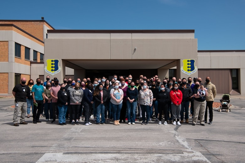 Staff from the 28th Medical Group pose for a photo outside of the medical facility after the launch of the new electronic health record system, MHS Genesis, at Ellsworth Air Force Base, S.D., April 24, 2021.