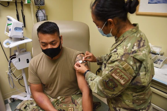 U.S. Air Force Master Sgt. Matthew Thomas, 627th Force Support Squadron first sergeant, sits while U.S. Air Force Tech. Sgt. Melan Davenport, 62nd Medical Squadron independent duty medical technician, prepares an area with an alcohol pad before administering a dose of a COVID-19 vaccination at the 62nd MDS Airmen's Clinic, Joint Base Lewis-McChord, Washington, April 14, 2021. Receiving the vaccine is voluntary for service members, however, all Department of Defense personnel and eligible TRICARE beneficiaries 16 years of age and older are encouraged to get vaccinated to protect their health, their families and their community. (U.S. Air Force photo by Senior Airman Mikayla Heineck)
