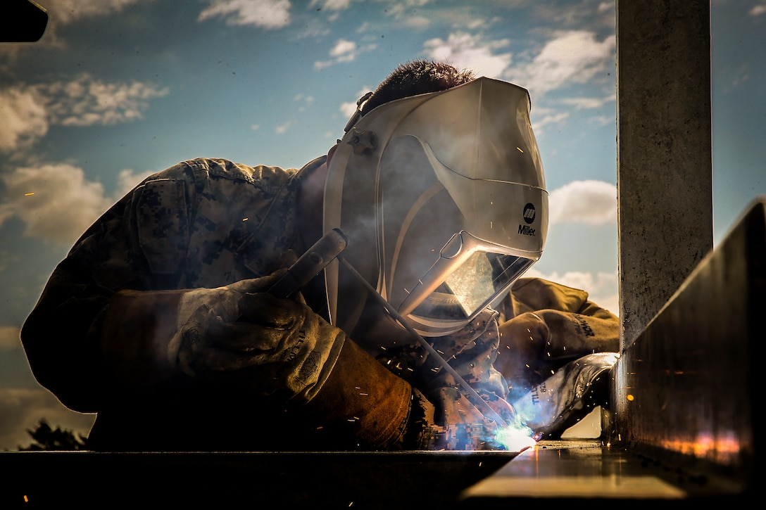 A Marine welds metals as sparks fly.