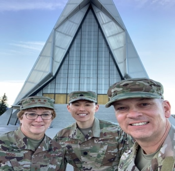 Three individuals stand in front of the Air Force Academy