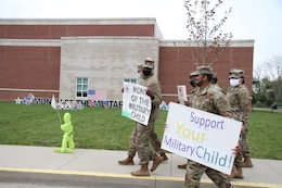soldiers hold signs supporting military children