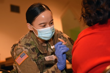 U.S. Army Spc. Melissa Bellgreen, a combat medic with the Michigan Army National Guard, assists the Genesee County Health Department at a vaccination clinic at a church in Flint, Michigan, April 9, 2021. Bellgreen came to the United States from China when she was a 1-year-old and became a U.S. citizen at the age of 8.