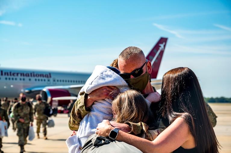 A family hugs near an aircraft.