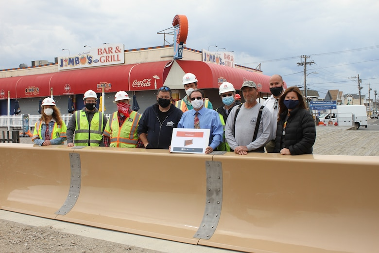 Team members pose in front of the removeable flood barrier in Seaside Heights, NJ