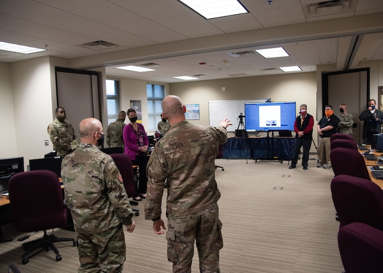 U.S. Air Force Capt. Matthew Riddle 315th Training Squadron officer in charge of the intelligence officer course team, center, showcases the Virtual Telecommunications system to Col. Andres Nazario, 17th Training Wing commander, left, in the Consolidated Learning Center on Goodfellow Air Force Base, Texas, April 15, 2021. This VTC was used to host intelligence leaders during a discussion about the intelligence career field. (U.S. Air Force photo by Staff Sgt. Tyrell Hall)