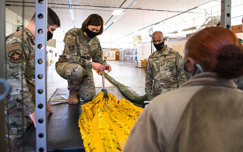 Chief Master Sgt. of the Air Force JoAnne S. Bass learns how to pack a B-52H Stratofortress parachute during her visit to Barksdale Air Force Base, Louisiana, April 22, 2021. Bass spent time with Airmen from across the installation, learning about their role in the mission of providing the nation with global strike capabilities. (U.S. Air Force photo by Airman 1st Class Jacob B. Wrightsman)