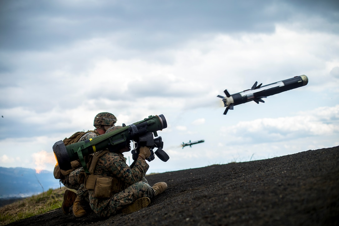 Marines sit on a hill and fire Javelin missiles, which fly through the air.