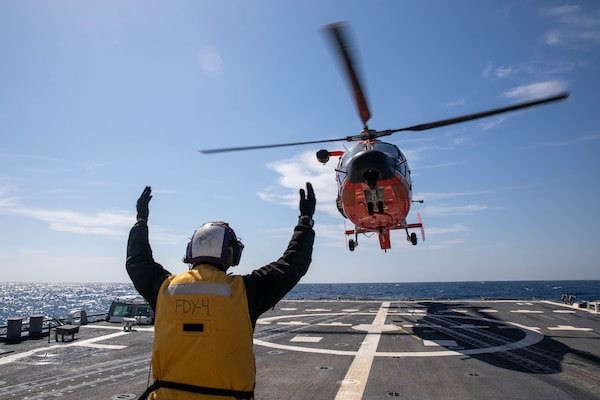 Boatswain's Mate 3rd Class Dillon Coakley guides an MH-65 Dolphin helicopter to land on the Arleigh Burke-class guided-missile destroyer USS Roosevelt (DDG 80) on April 26, 2021.