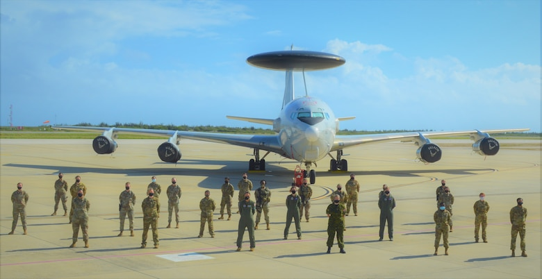 group photo of people in front of aircraft
