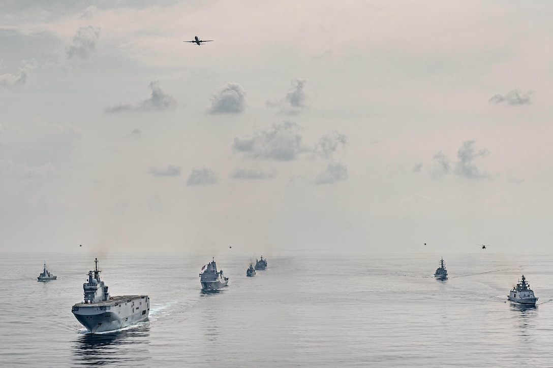 A fleet of ships sails in the sea.