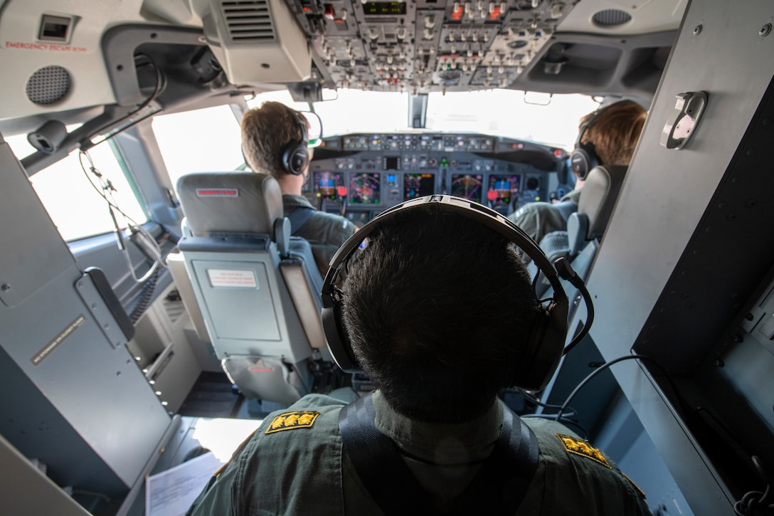 A three-person crew operates in an aircraft flight deck.