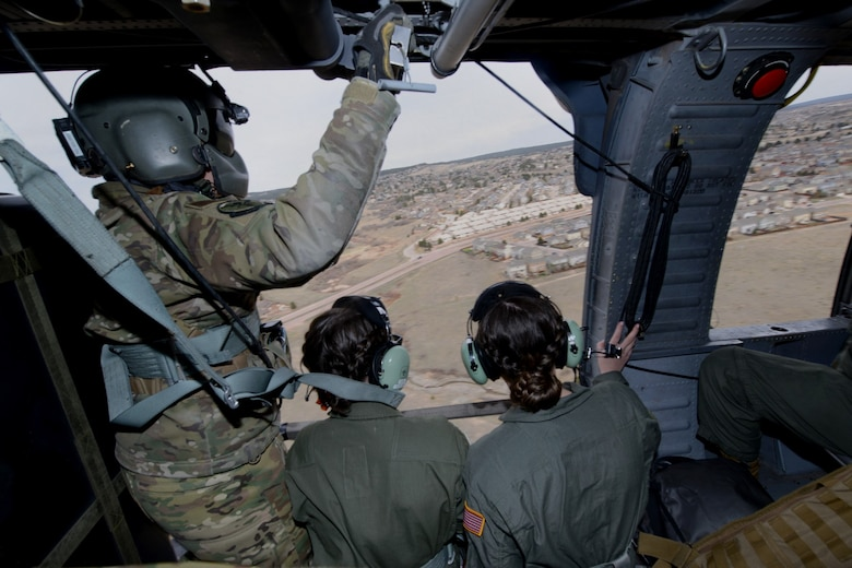 Cadets and a special missions' aviator (left) fly aboard an HH 60-G helicopter above Colorado Springs
