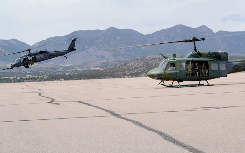 An HH 60-G helicopter lifts off from the airfield at the U.S. Air Force Academy while a UH-1 N gets ready to follow during