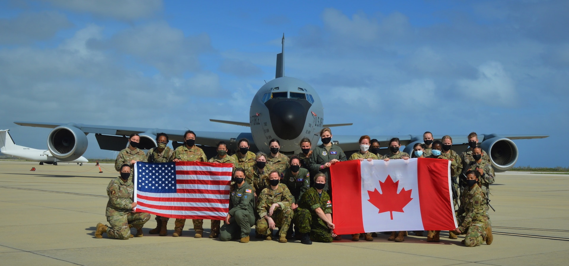 group photo of people in front of an aircraft