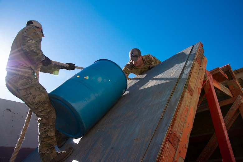 Two U.S. Air Force Tactical Air Control Party specialists carry a drum over an obstacle during the 2021 Wraith Challenge, April 20, 2021, on Fort Bliss, Texas. This was one of six obstacles in the leadership course. (U.S. Air Force photo by Airman 1st Class Jessica Sanchez)