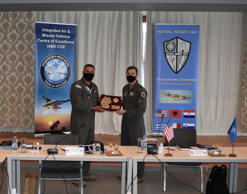 Hellenic Air Force Col. Evangelos Tzikas, Integrated Air and Missile Defense Center of Excellence director (left), receives an appreciation gift from U.S. Air Force Maj. Gen. Greg Semmel, Air National Guard assistant to COMUSAFE and ASTRAL KNIGHT 21 exercise director, on behalf of the participants of the Command and Control Commanders Conference in Chania, Crete on April 21, 2021. Commanders from six NATO nations attended the two-day conference to discuss IAMD coordination in the southern European region, in preparation for the upcoming USAFE-led exercise, AK21.