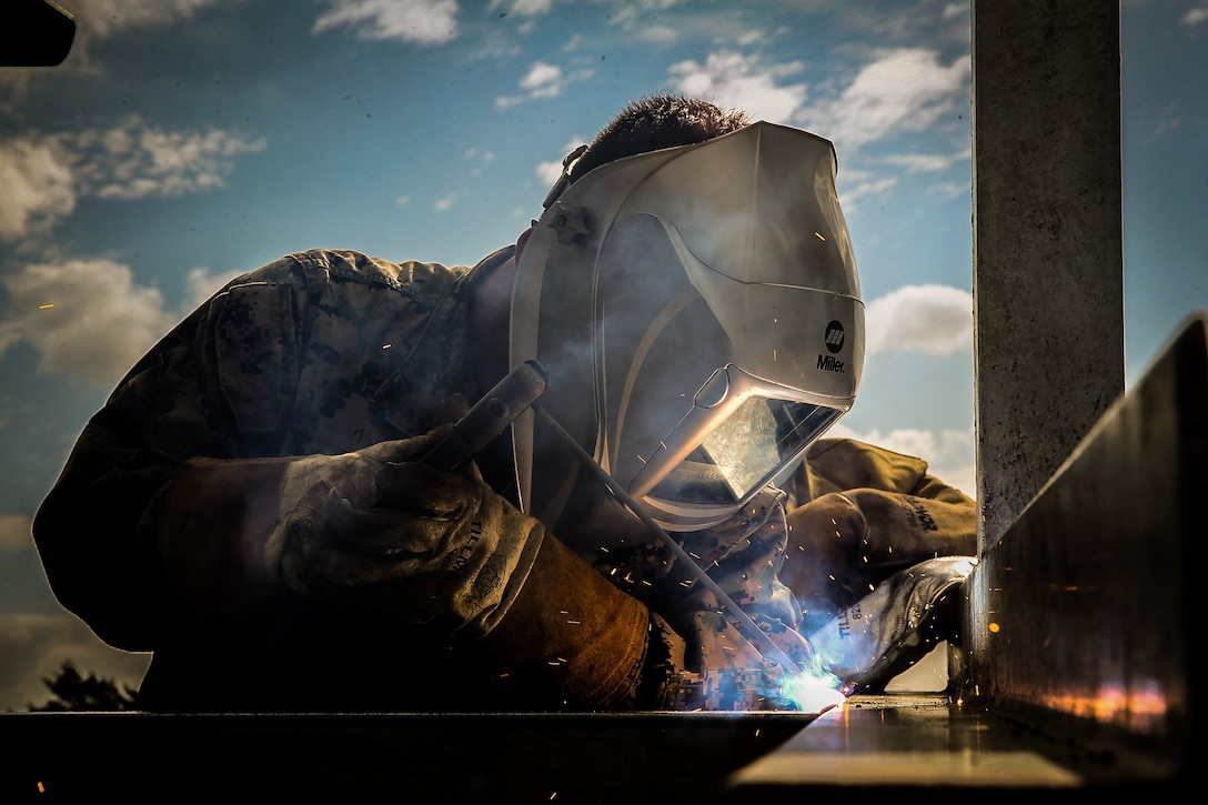 A U.S. Marine welds pieces of metal together on Kin Blue training area, Okinawa, Japan, April 20.