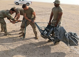 Riggers of the Fort Bragg, North Carolina, based 151st Quartermaster Company, deployed the U.S. Central Command area of responsibility in support of 1st Theater Sustainment Command, work to recover one of four Joint Precision Air Delivery System, or JPADS, units used to air drop four bundles  at the Camp Buehring, Kuwait, drop zone. The black device rigged between the parafoil and the payload is the Modular Autonomous Guidance Unit, or MAGU, which uses the lines of the chute to steer it to its programmed target.