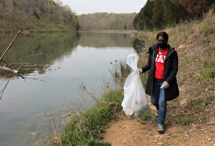men and women gathering garbage and debris in the woods.