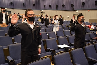 Sailors and civilians at Commander, Fleet Activities Yokosuka (CFAY) recite the oath of allegiance during a United States Citizenship and Immigration Services (USCIS) naturalization ceremony.