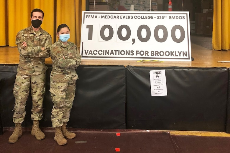 Two Air Force members stands in front of a sign reading 100,000 vaccinations for Brooklyn.