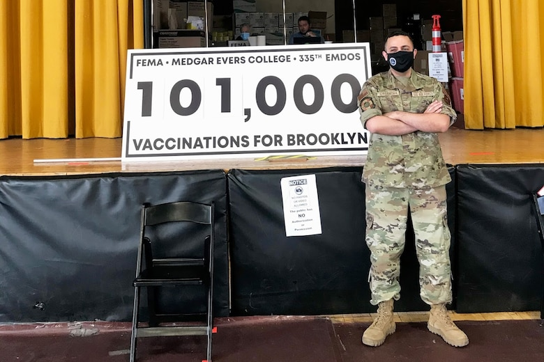 An Air Force Staff Sgt. stands in front of a sign reading 101,000 vaccinations for Brooklyn.
