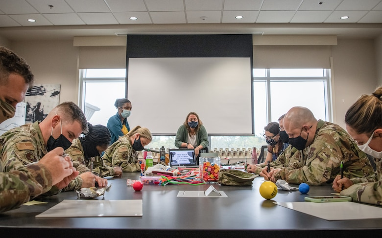 A group of Airmen sit at a table and write on notepads as a civilian woman watches.
