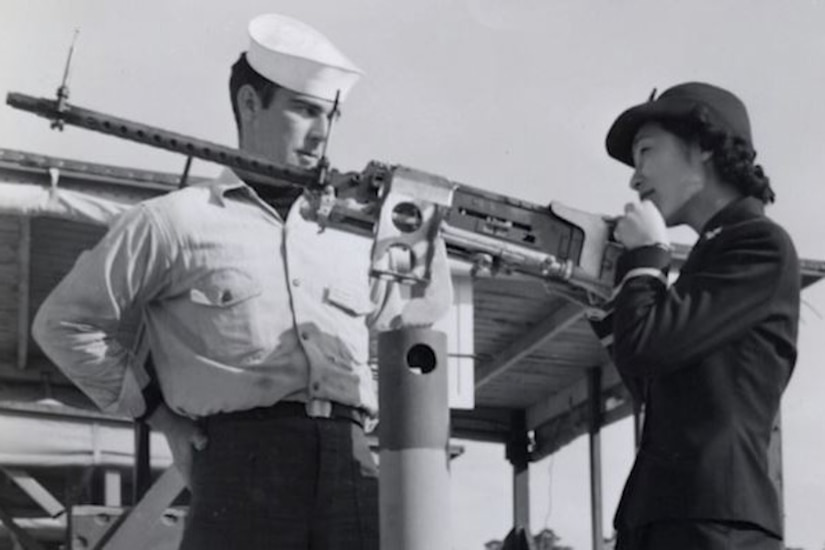 A man in uniform watches a woman in uniform as she looks through the scope of a long gun.