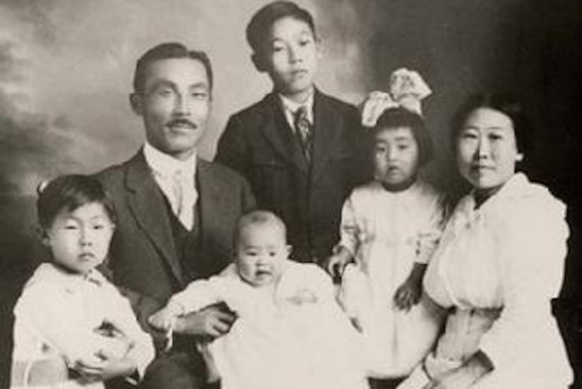 A couple and four small children dressed in early 20th century clothing pose for a photo.
