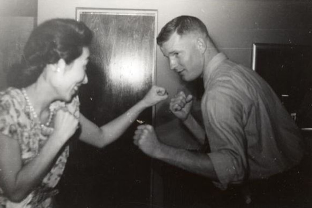 A woman and a man each put up their fists like they're play-fighting.